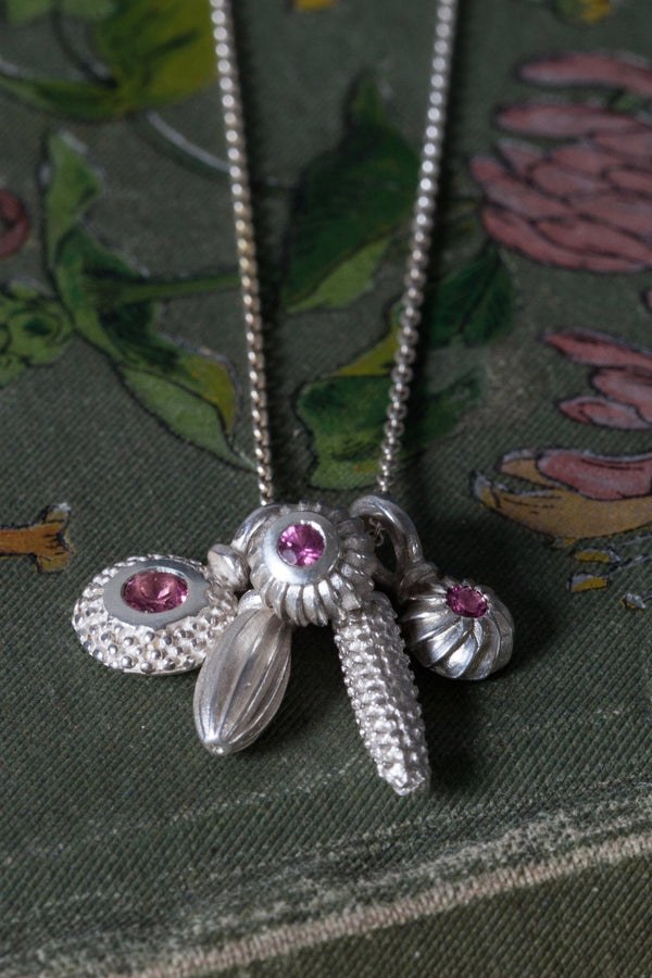 A dainty pendant with a cluster of 5 silver pollen charms 3 set with a Pink Tourmaline October's birthstone