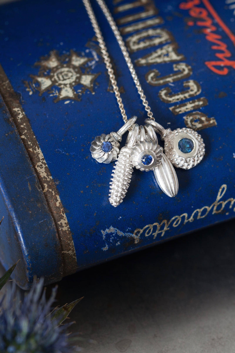 A dainty pendant featuring 5 silver pollen 3 set with a Sapphire, September's birthstone