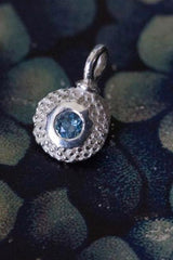 A bobbled pollen charm in silver with a sparkling aquamarine, March's birthstone.