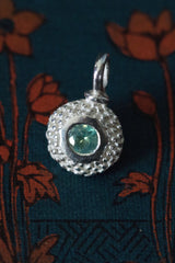 A bobbled pollen charm in silver with a fascinating changeable green-red alexandrite, June's birthstone.