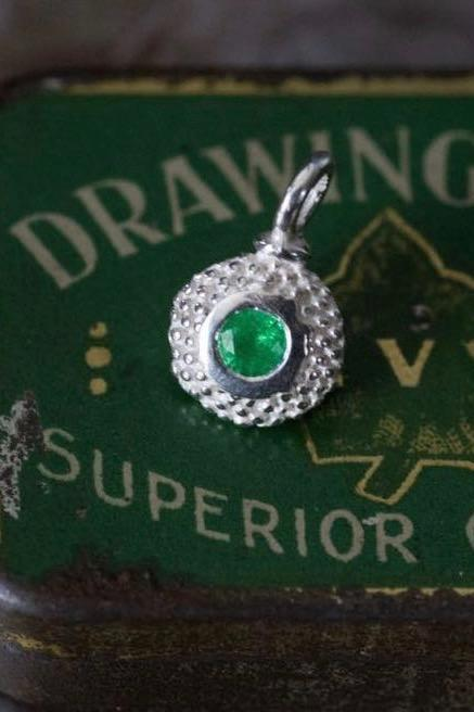 A bobbled pollen charm in silver with a gorgeous green emerald, May's birthstone.