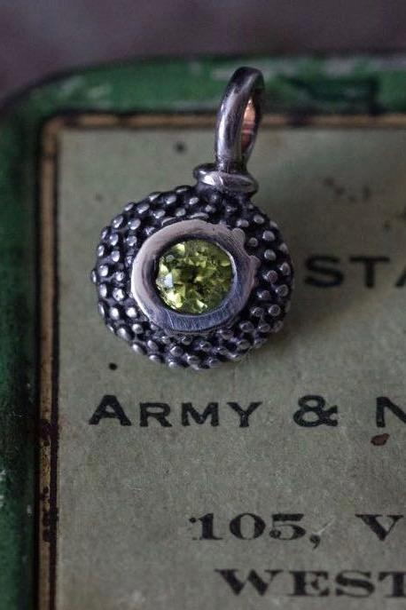 A bobbled pollen charm in oxidised silver with a glistening green peridot, August's birthstone.