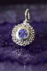 A bobbled pollen charm in silver with a fabulous tanzanite, December's birthstone.