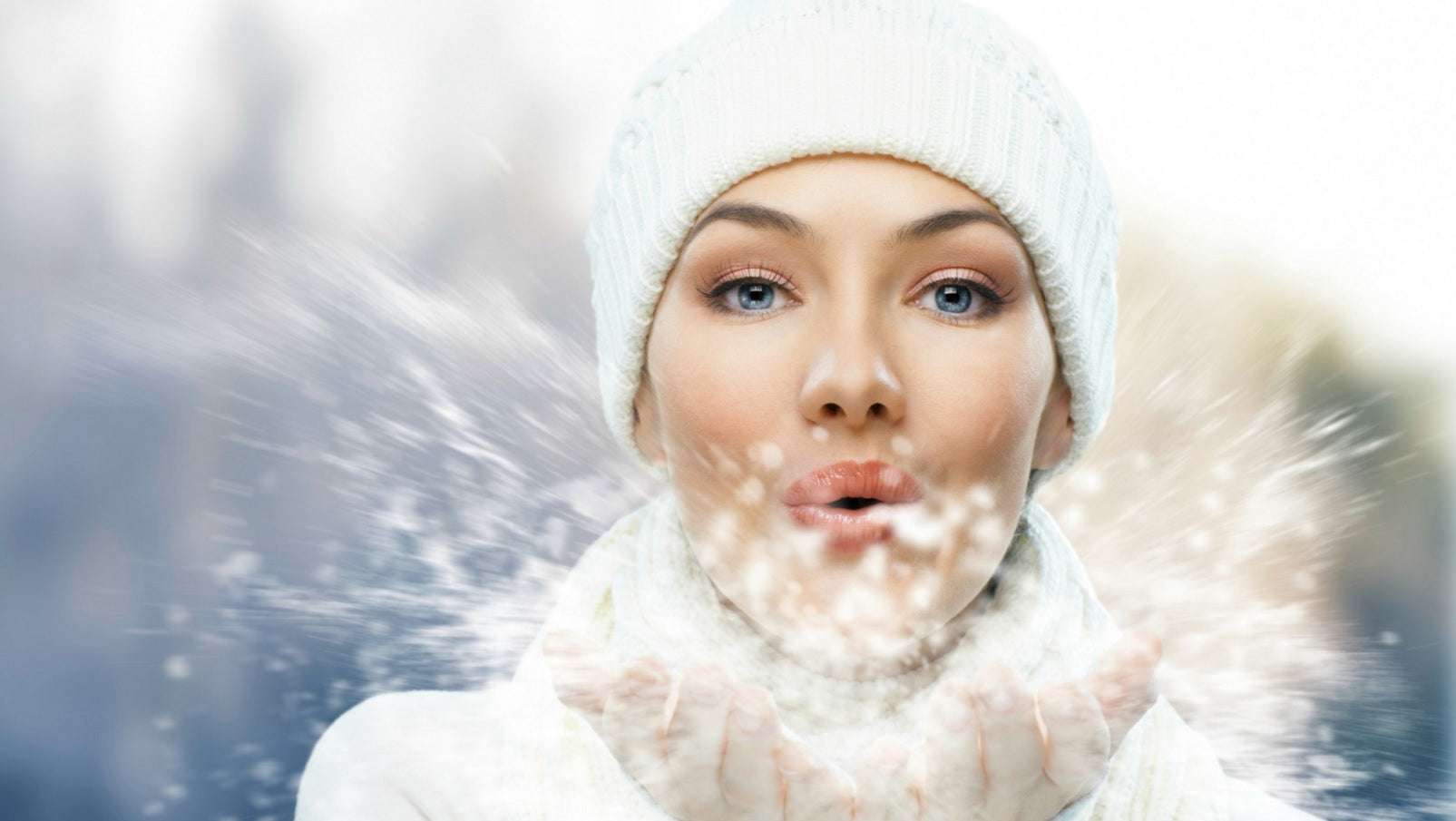 Woman blowing snowflakes from here hands