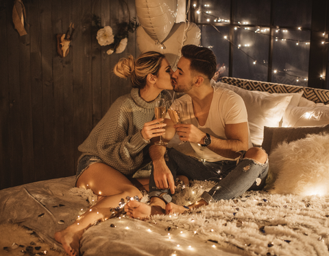 Couple kissing on bed with string lights