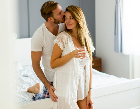 Couple dressed in white kissing
