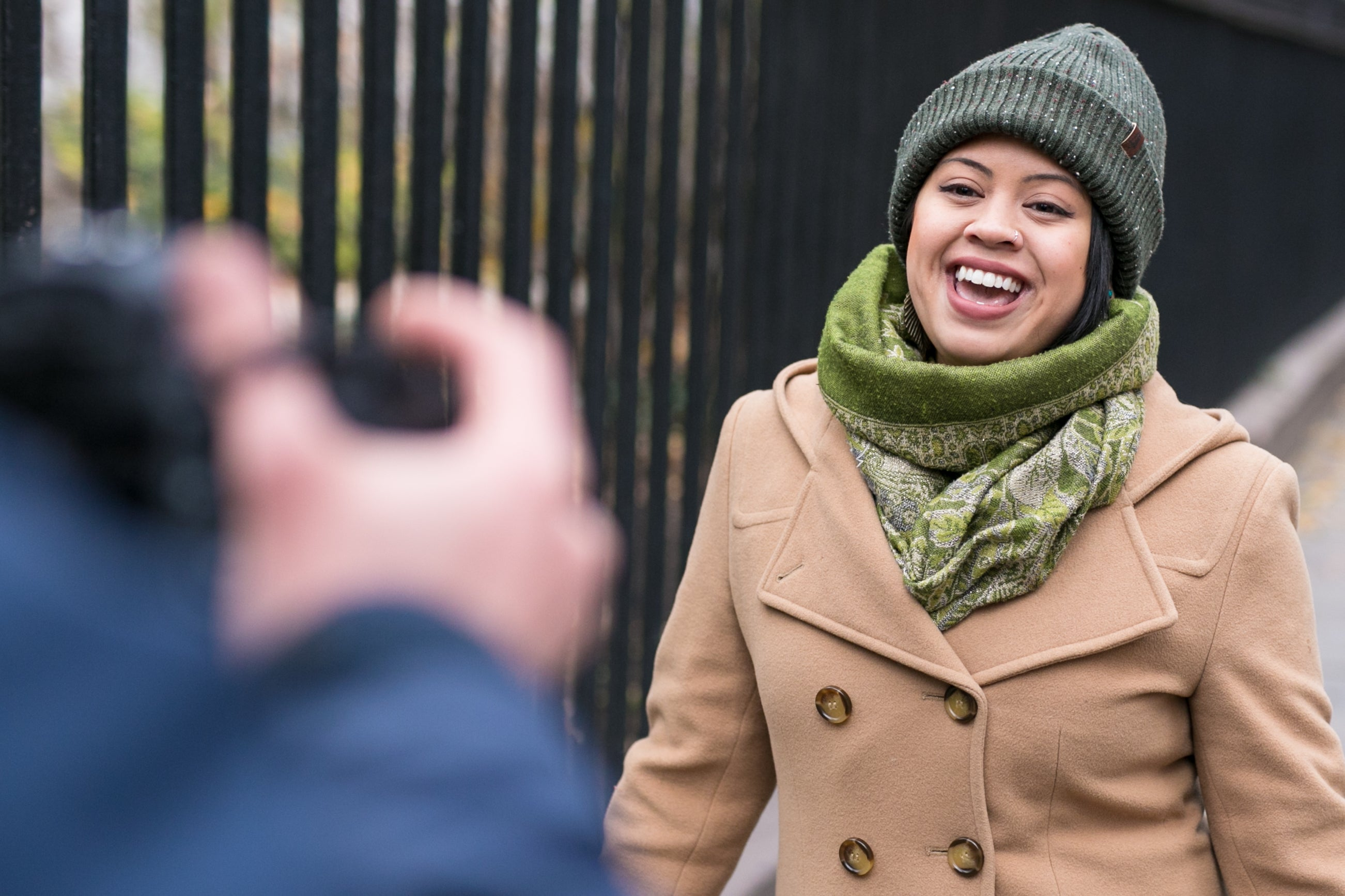 Kristian wrapped in a green scarf and beanie and tan coat singing joyfully at a camera in the streets.