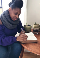 Andriea Denise writing in a journal in New York City (2018)