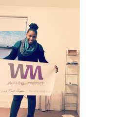 Andriea Denise holding first Write Mind Studio banner at first office