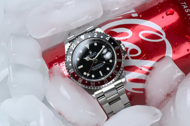 vintage rolex gmt master coke laying on a can of coke on ice