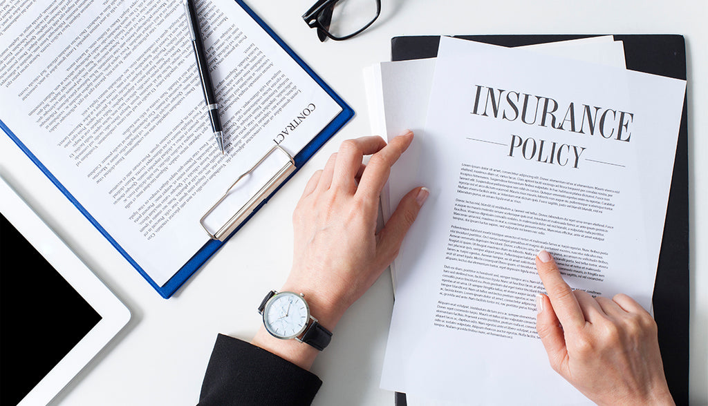 woman wearing a watch pointing to insurance policy laying on table