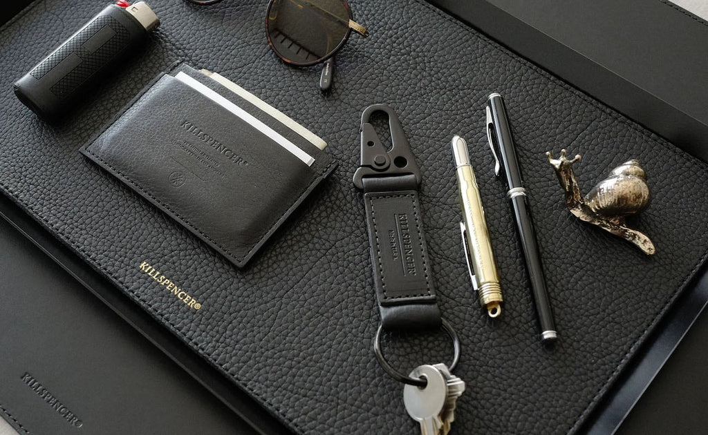 black leather valet tray displaying personal items
