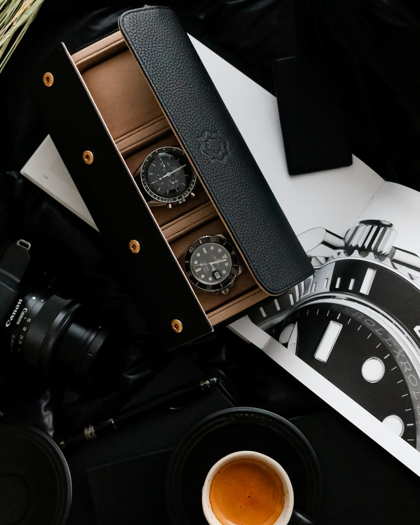 black watch roll with rolex submariner and omega speedmaster sitting on top of rolex catalog