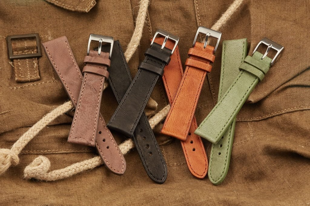 four high quality leather watch straps sitting on leather background