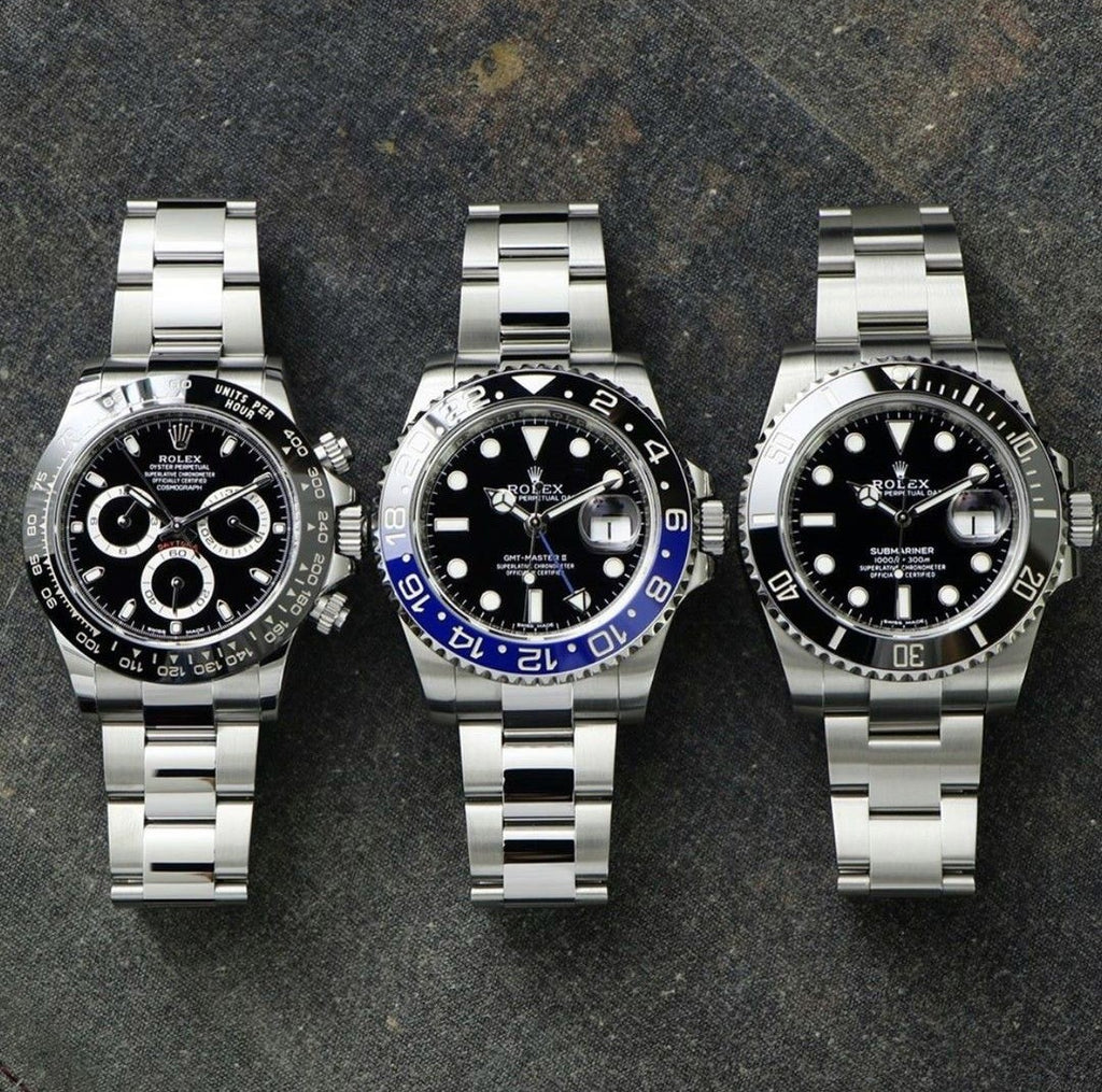 rolex daytona, gmt master ii, and submariner laying on a table
