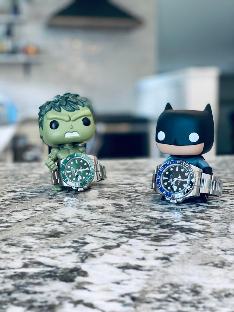 rolex gmt master II batman and green submariner hulk laying on counter top with hulk and batman pop figurines