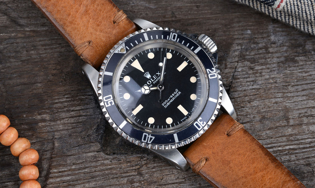 vintage rolex submariner laying on table with leather strap