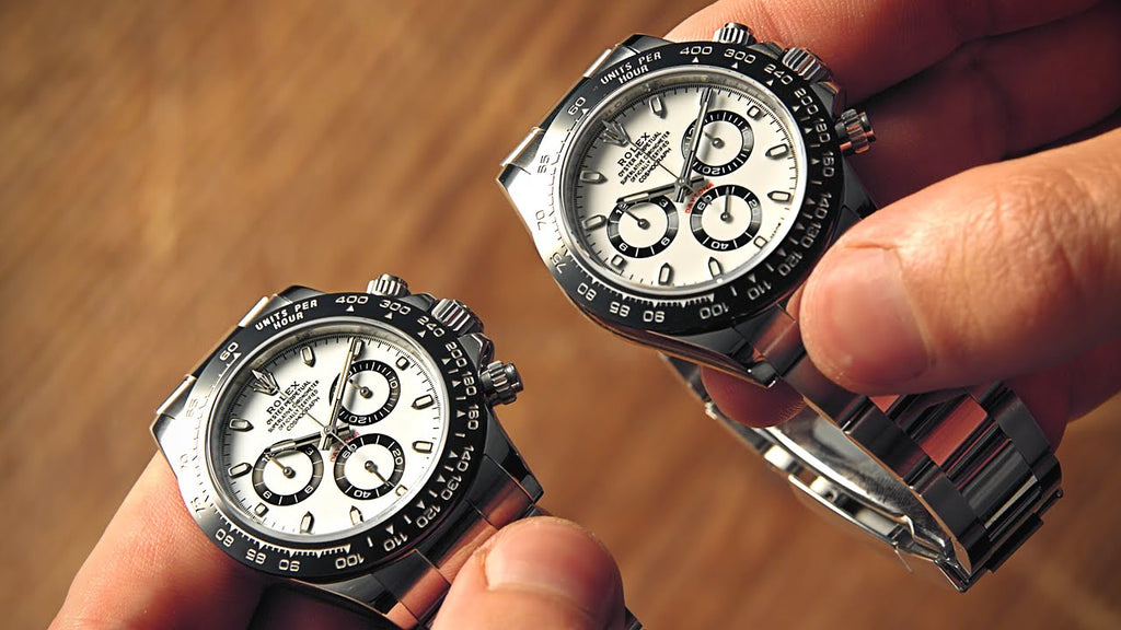 Someone holding two stainless steel Rolex Daytona next to eachother, one of them being fake and the other is real
