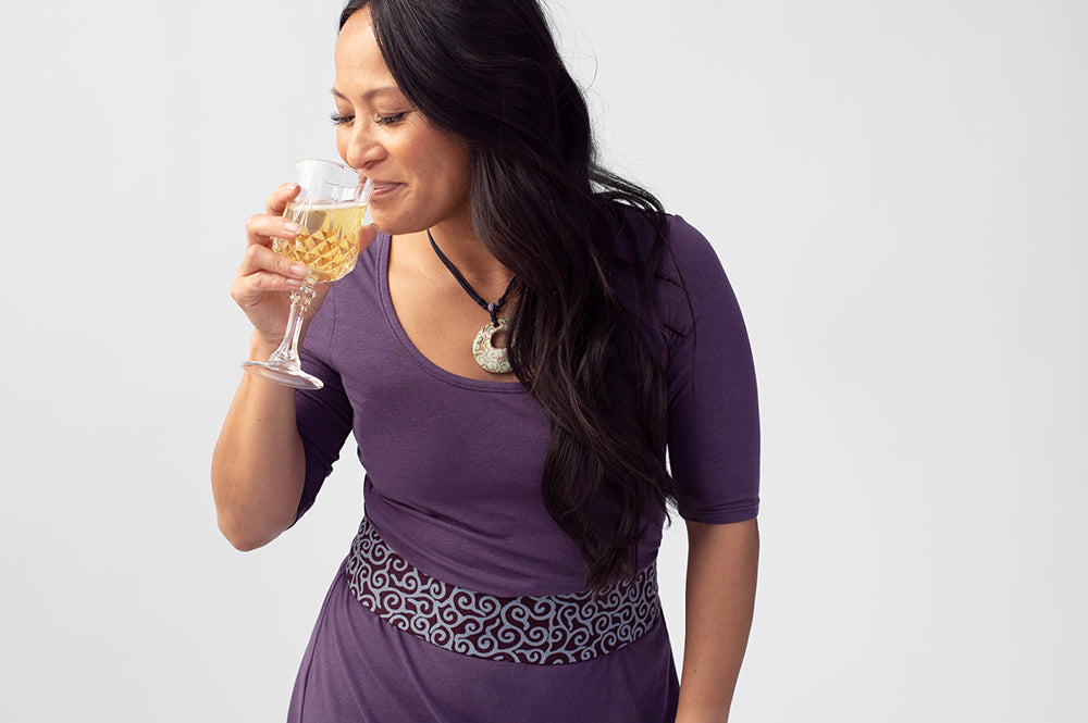 Woman wearing purple dress and purple patterned belt, drinking from a glass