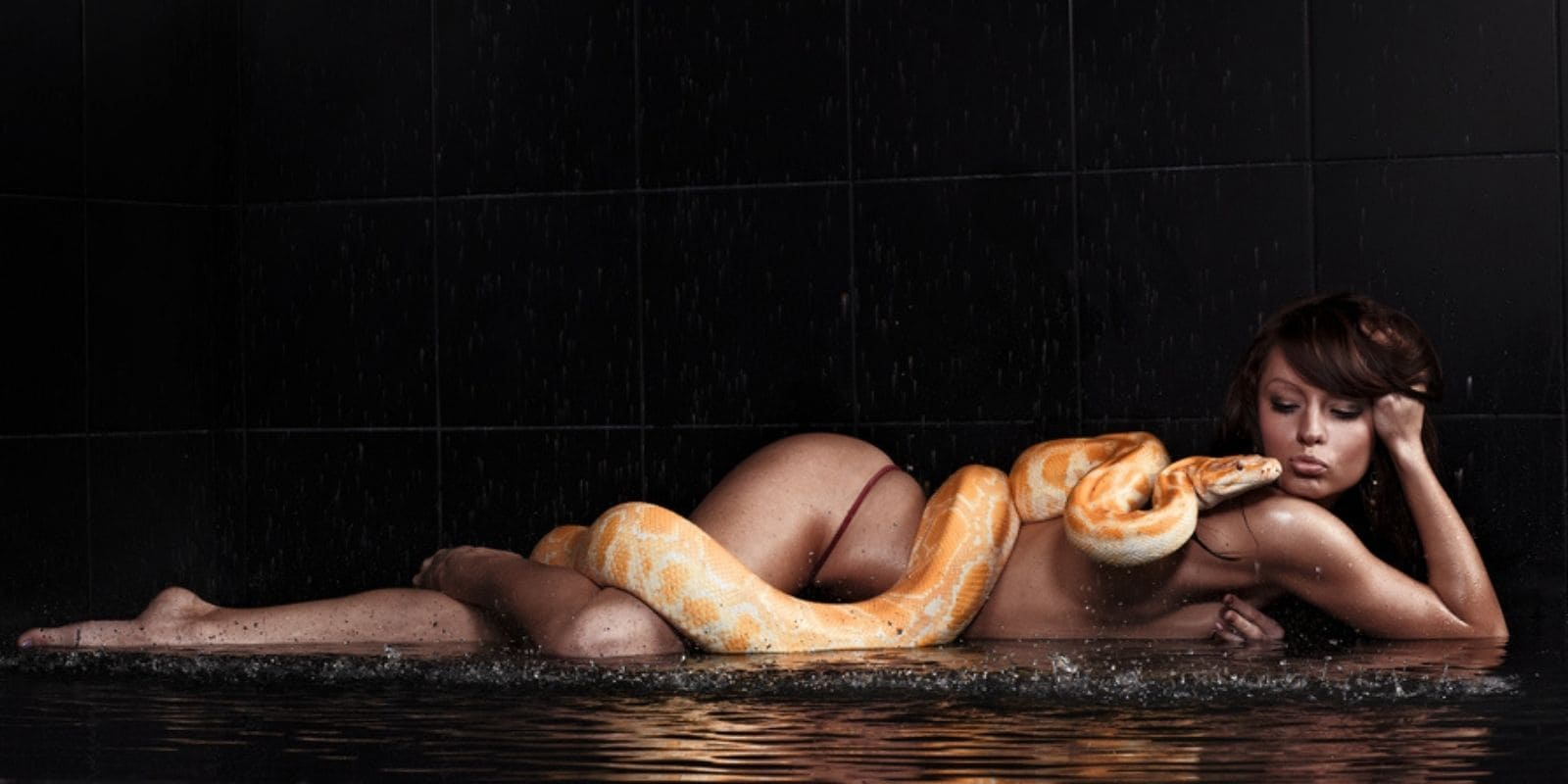 Woman lays on the ground kissing a huge snake