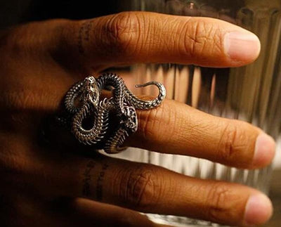Snake ring on a man hand holding a glass