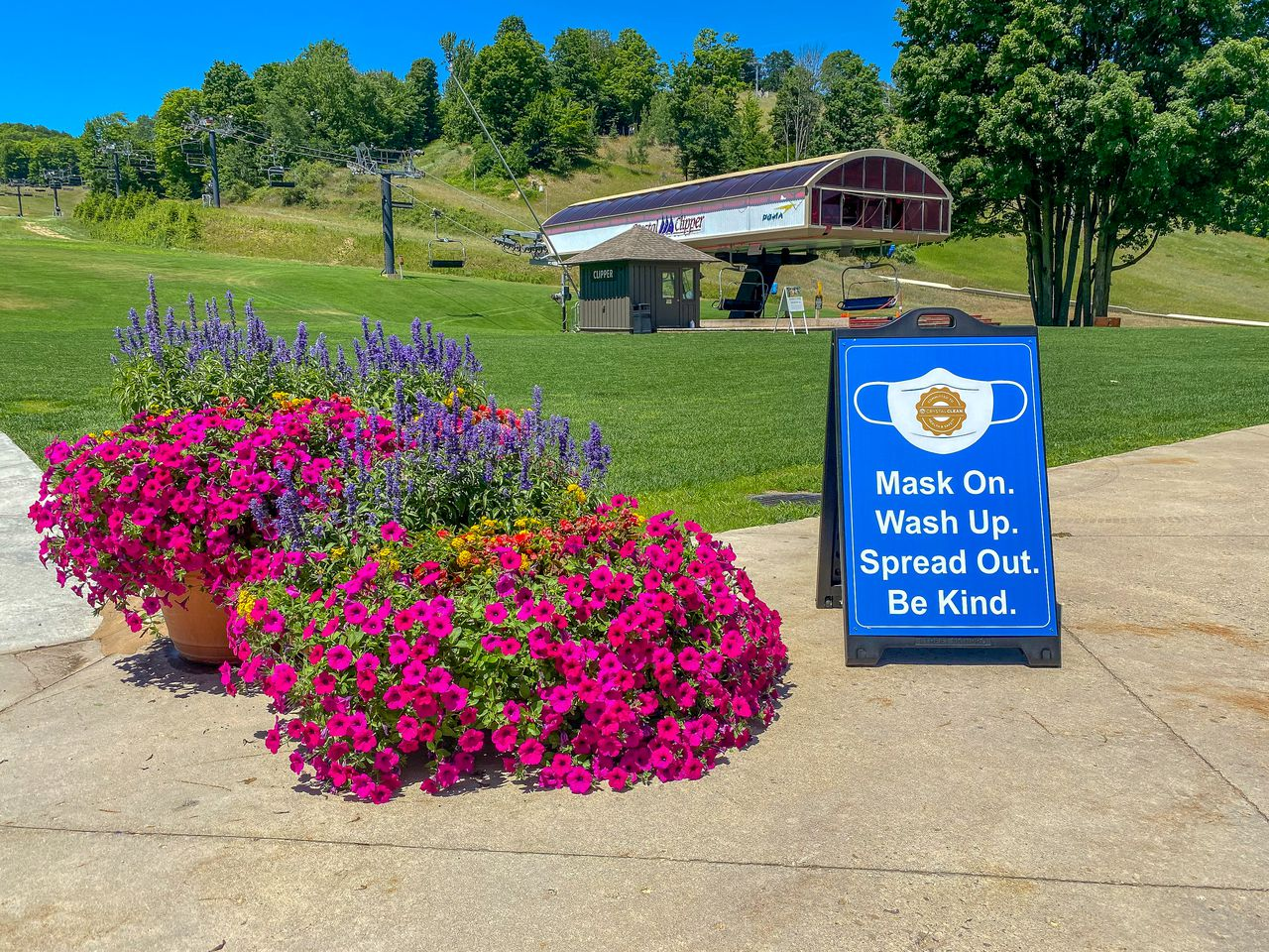ski lift in the summer with sign that says mask on. wash up. spread out. be kind.
