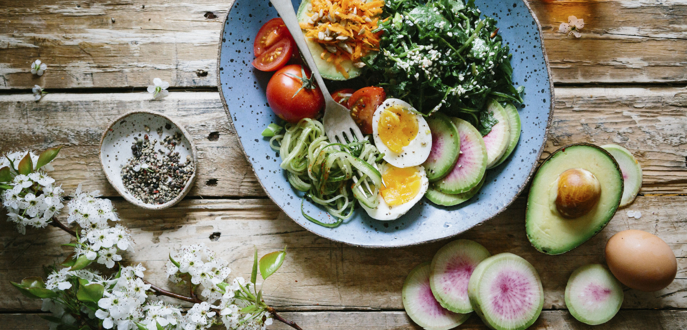 Table full of magnesium-rich foods like spinach, avocado, and other unprocessed foods.