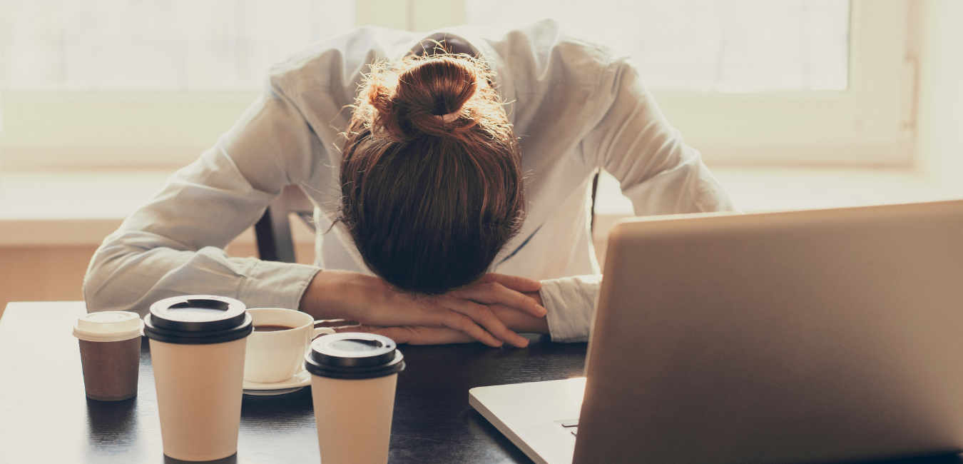 Woman suffering from chronic fatigue with head down and coffee cups in front of her apple computer.