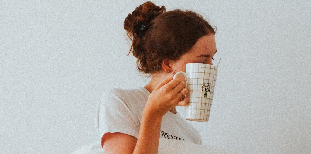 A girl with a cup of tea and a pillow