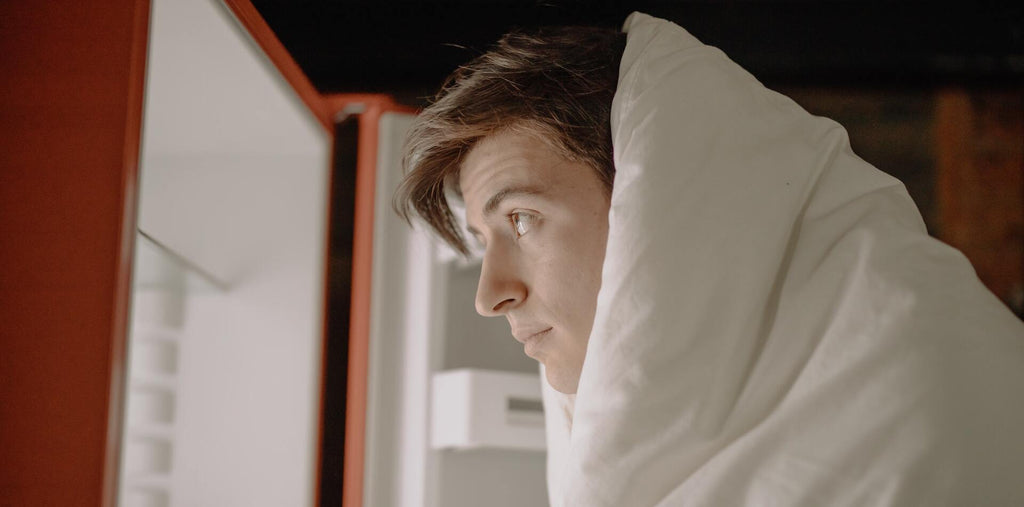 A man looking in the fridge covered in the blanket