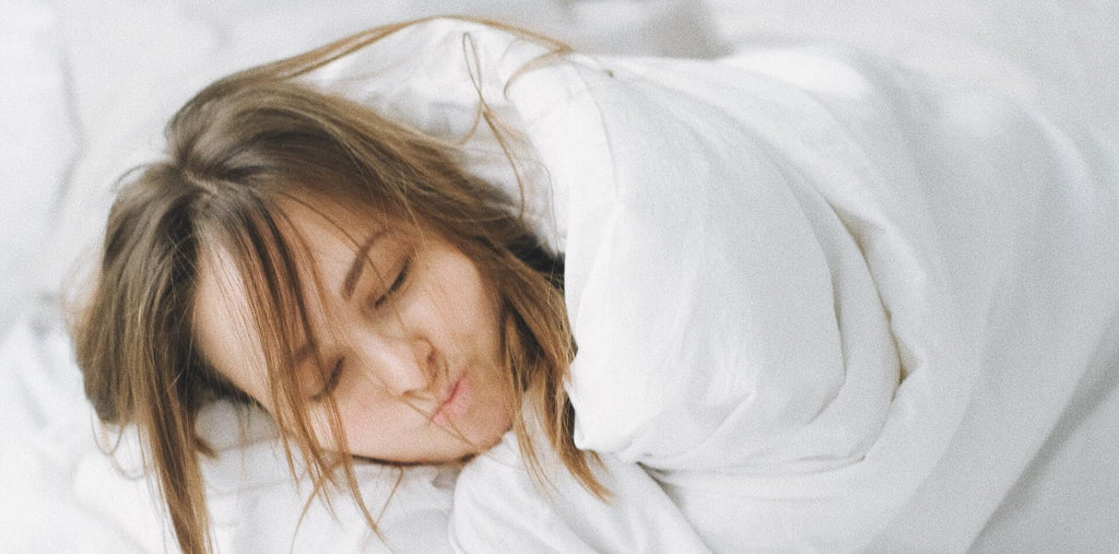 A cheerful woman covered in the white blanket