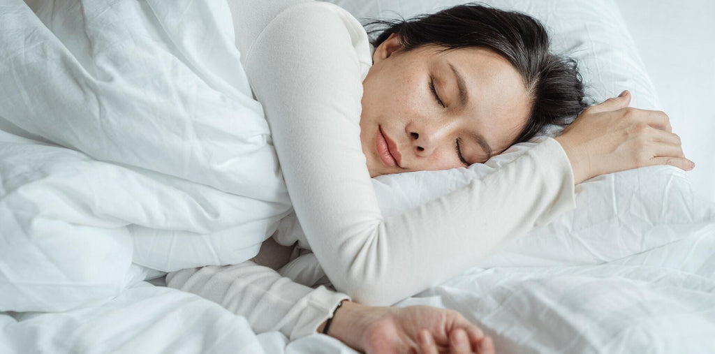 A woman calmly sleeping on white sheets