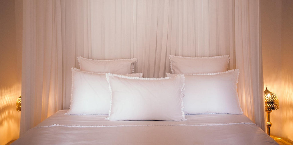 A bed with three pillows and cozy light around
