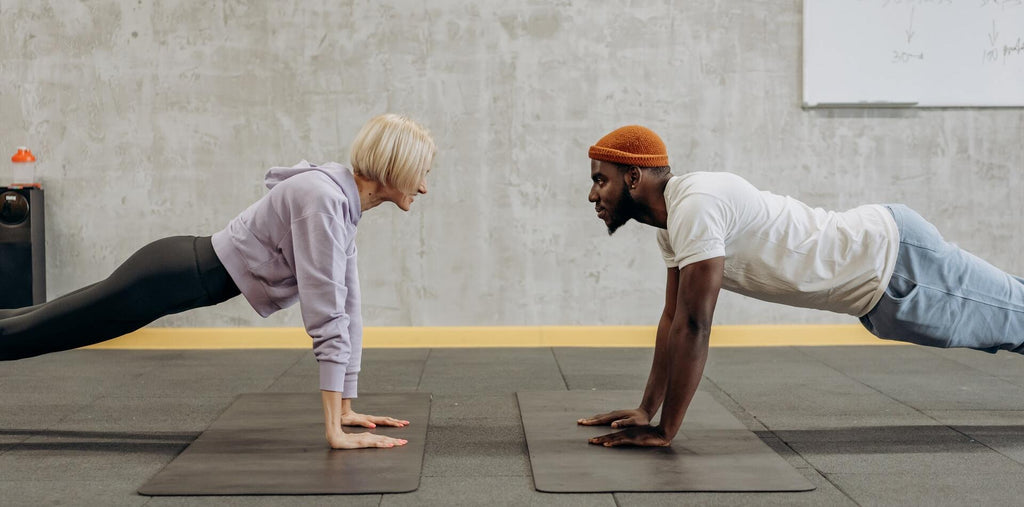 Man and woman standing in a plank next to each other