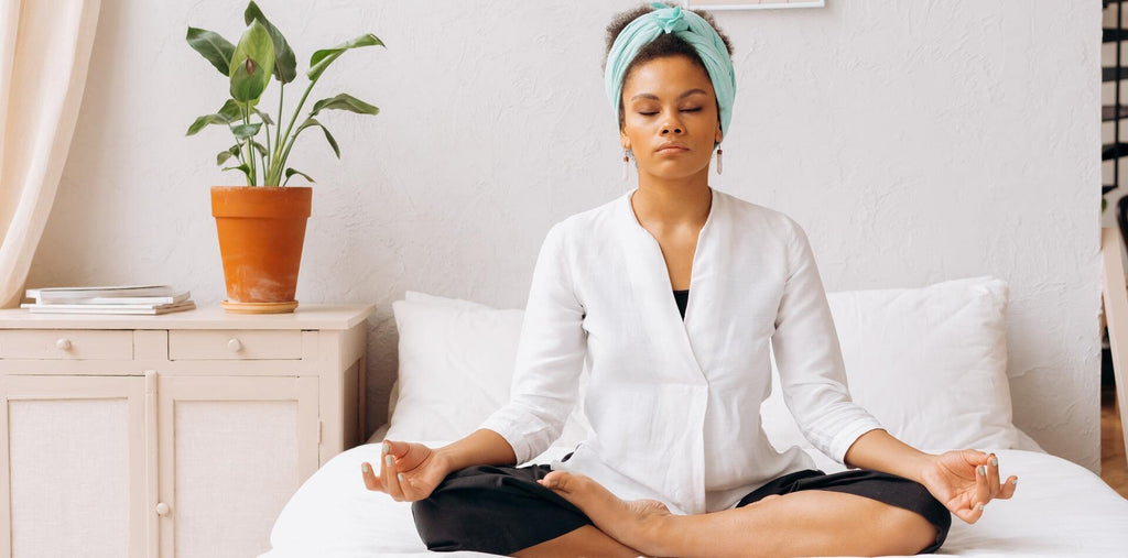 A woman meditating in her bed before going to sleep