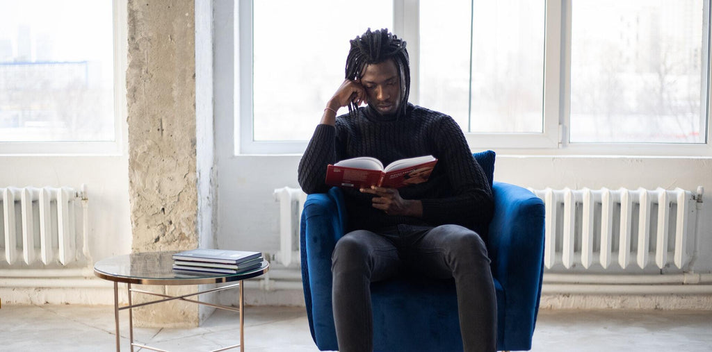 A reading man sitting in a chair in his living room