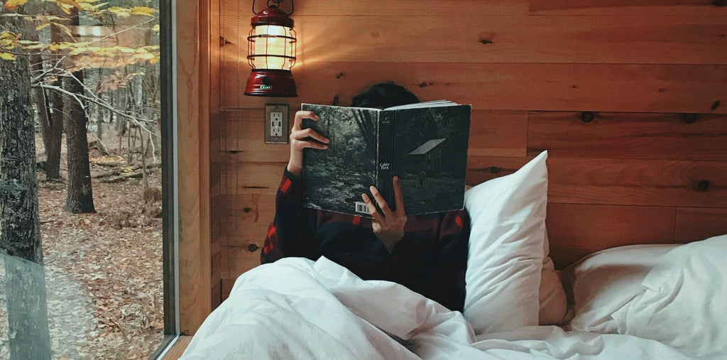 A person reading the book laying in a bed