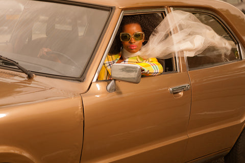 Vintage 70s fashion afro woman with sunglasses driving