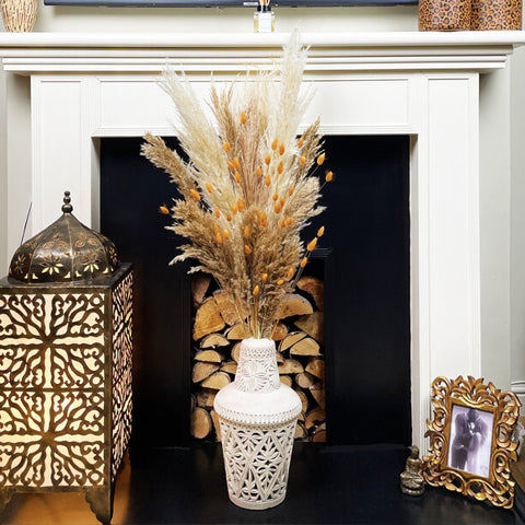 Pampas grass and bunny tails styled in vase on fireplace