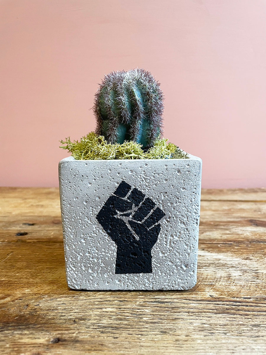 Small concrete vase featuring black power sign