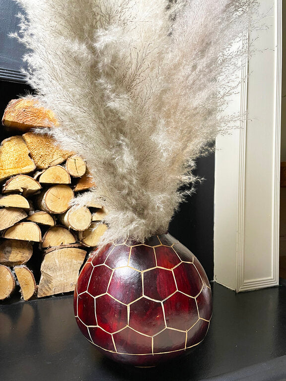 Natural burgundy calabash vase with pampas grass on fireplace