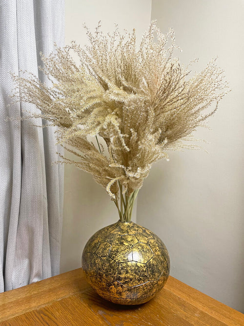 Gold calabash vase with natural reed grass on wooden table