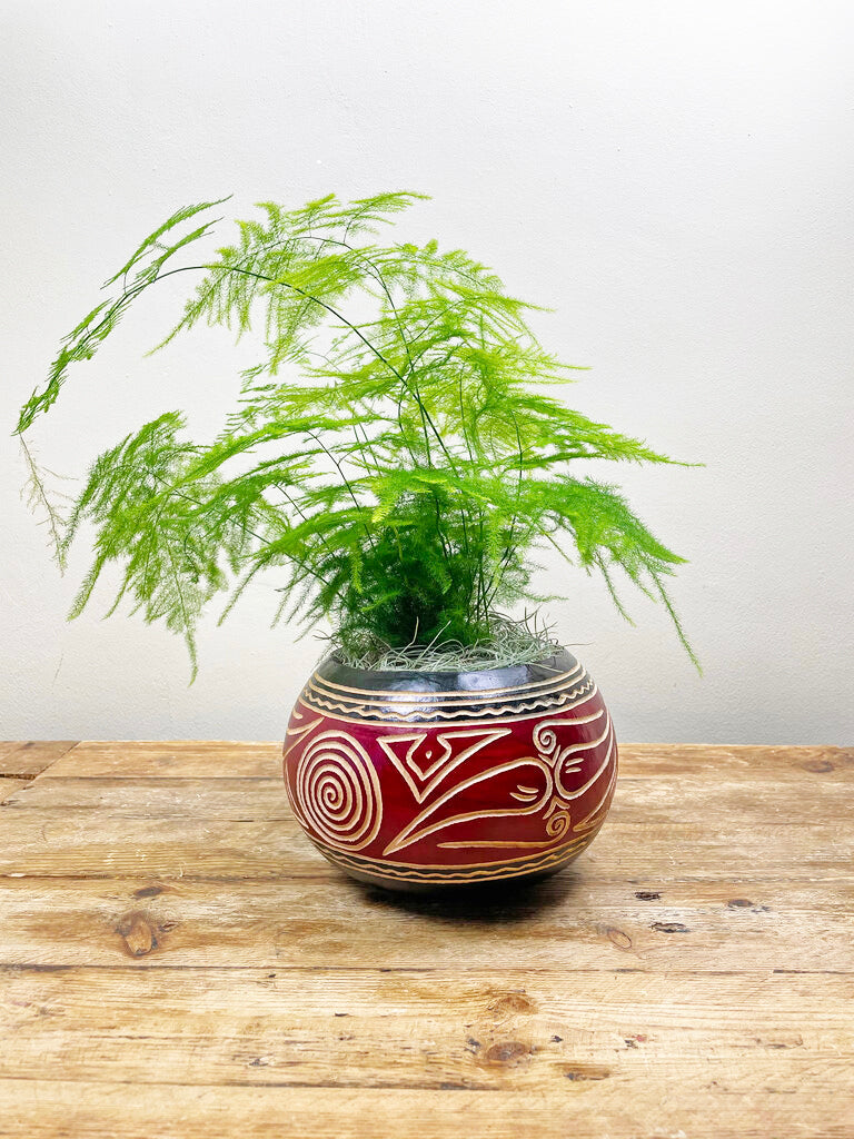 Red and Black calabash pot on wooden table