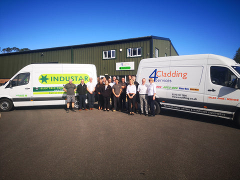 Cladding Mate & 4 Cladding Service team photo. Standing in the premises in front of two vans.