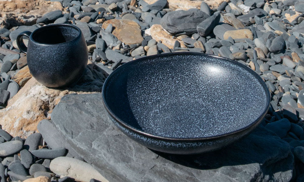Close-up of a matte black cup and a matte black pasta plate on a rocky background on the beach in Portugal.