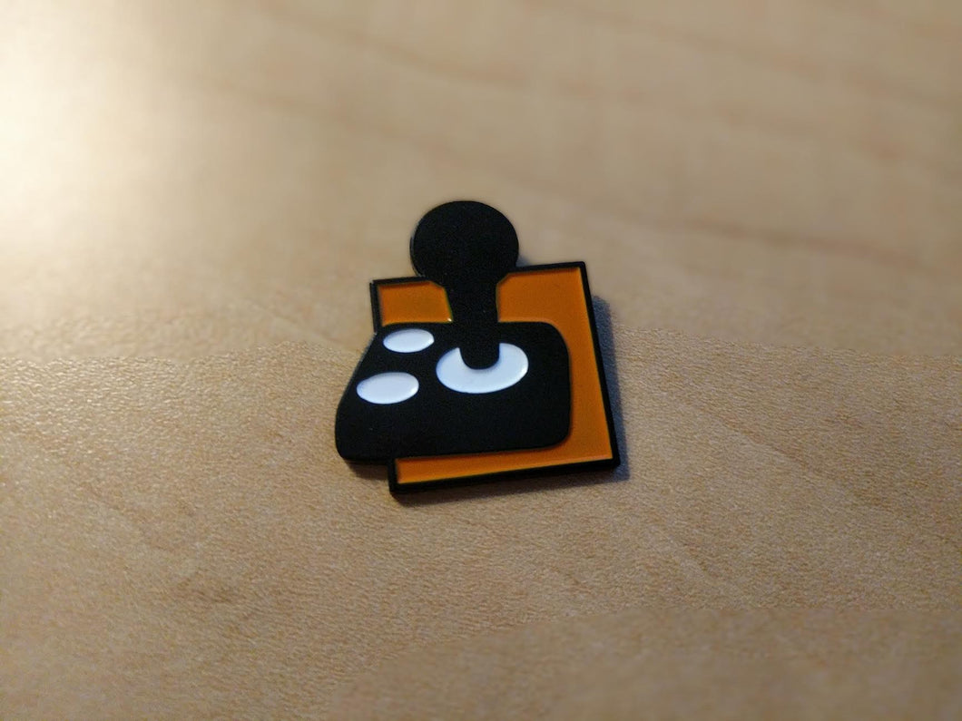 A black joystick with two white buttons on an orange background.
