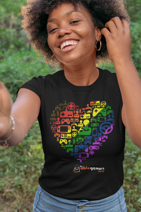 An African-American women wearing a black t-shirt. On the shirt is a heart made up of the AbleGamers logo, and came controller icons. The heart is colored in a rainbow, starting with Brown in the upper left to purple in the lower right. AbleGamers is at the bottom, and