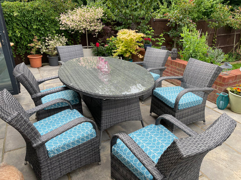 A set of six odd shaped garden chair cushions in an Orla Kiely duck egg blue fabric on mid grey wicker chairs around a glass topped dining table, outside in a lush green garden.