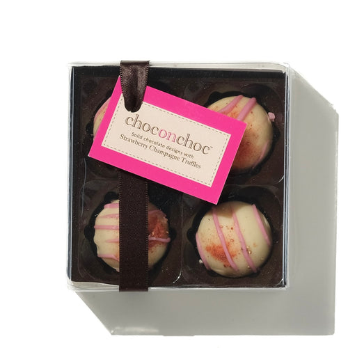four white chocolate strawberry champagne truffles in a box