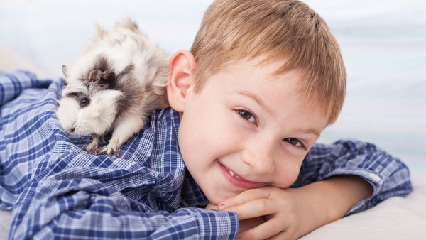 smiling child bonding with a guinea pig that is sat on their shoulder